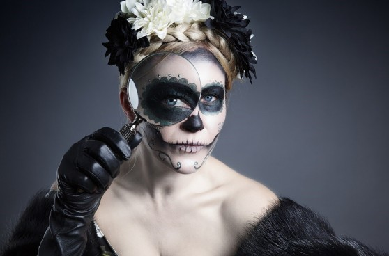 Woman in skull make-up with a magnifying glass